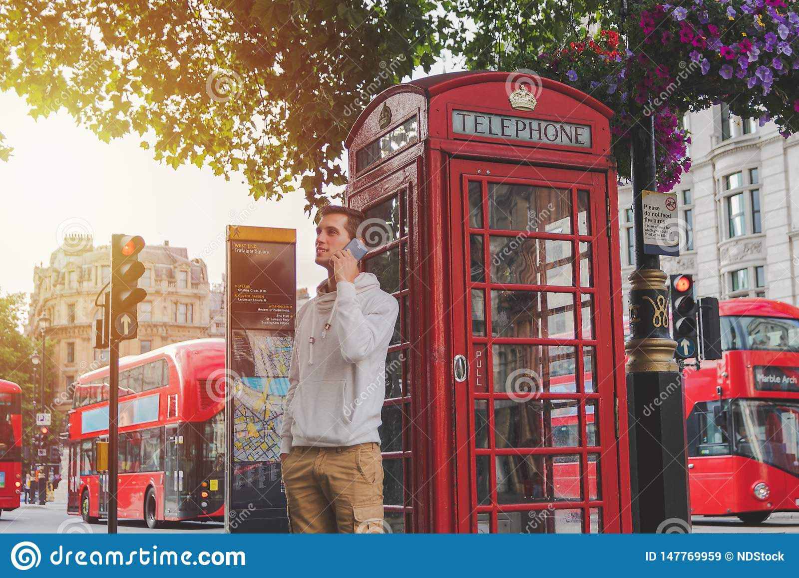 Muchacho joven que usa el smartphone delante de una caja del teléfono y de un autobús rojo en Londres
