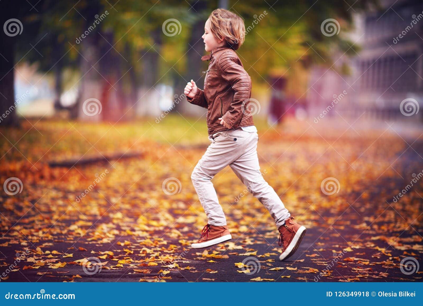 Muchacho joven sonriente, niño que se divierte en parque de la ciudad del otoño entre las hojas caidas