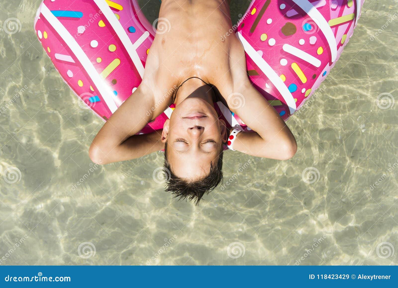 Muchacho lindo con el buñuelo inflable en piscina