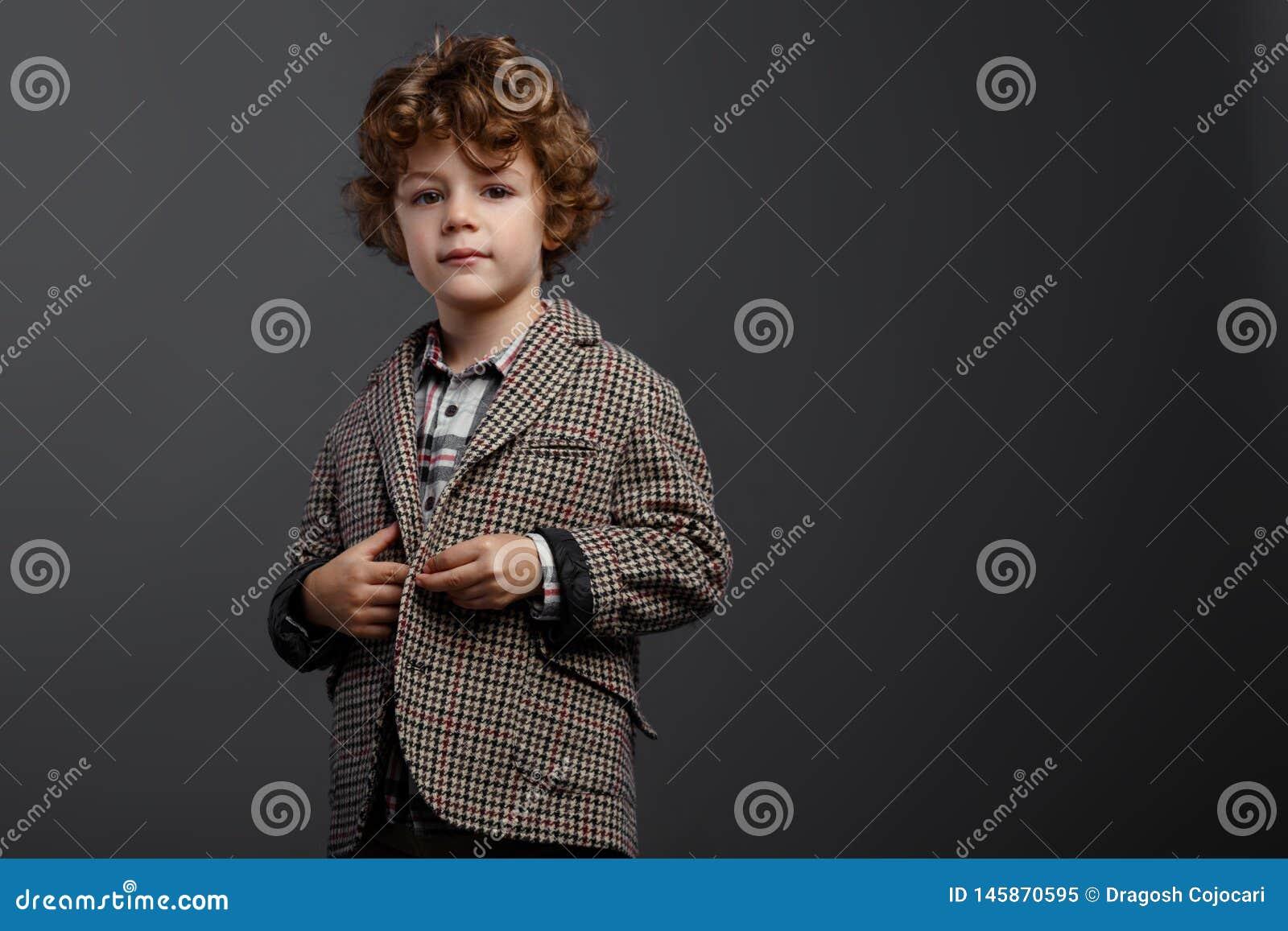 Muchacho lindo contentado del muchacho con el pelo rizado rojo vestido en un traje elegante, en un fondo gris, con el espacio de