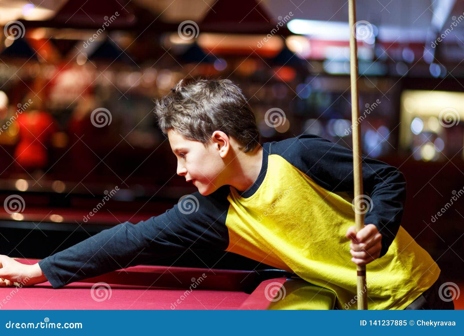 Muchacho lindo en billar amarillo de los juegos de la camiseta o piscina en club El muchacho aprende jugar el billar Muchacho con