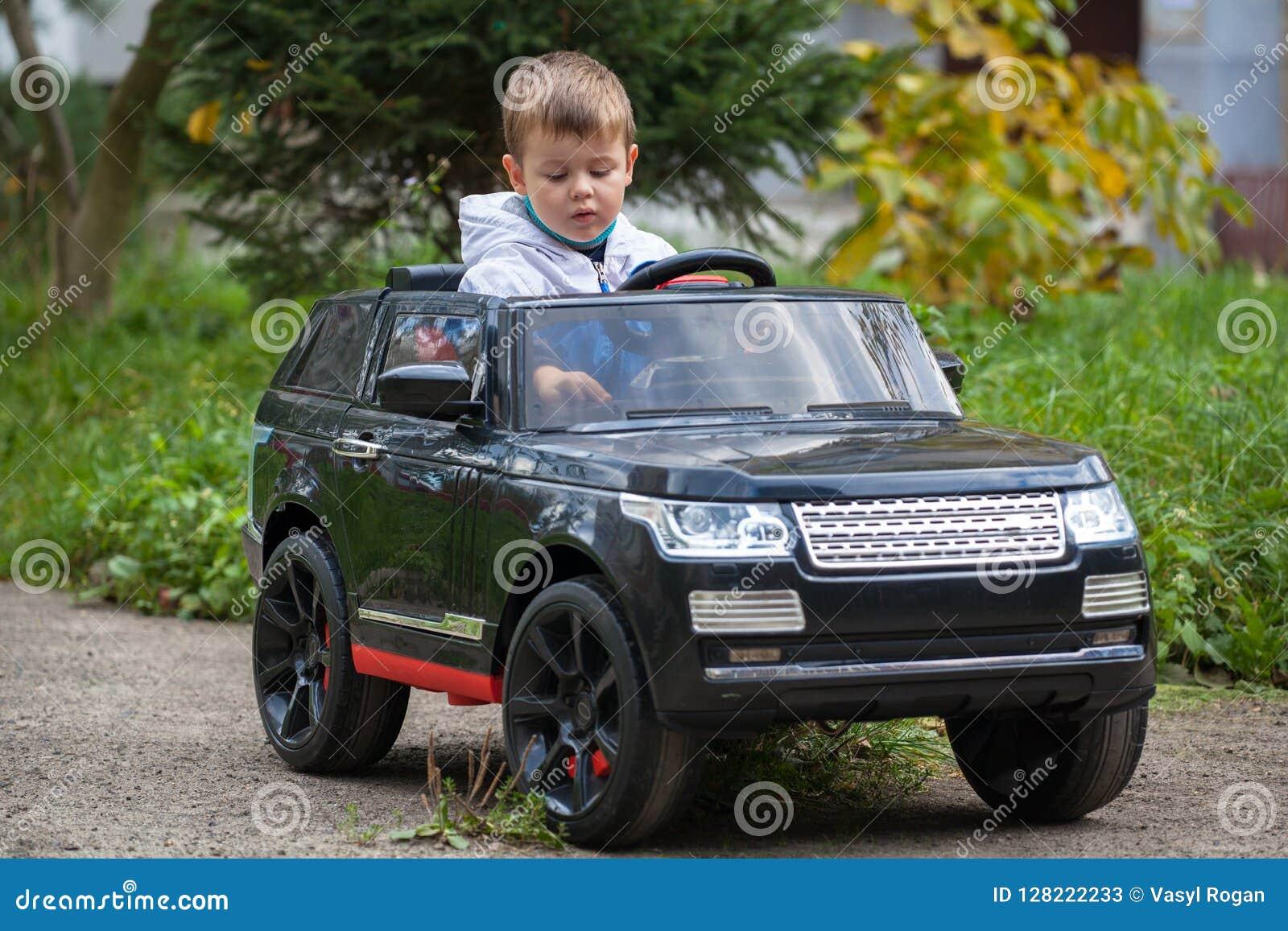 Muchacho lindo en montar un coche eléctrico negro en el parque
