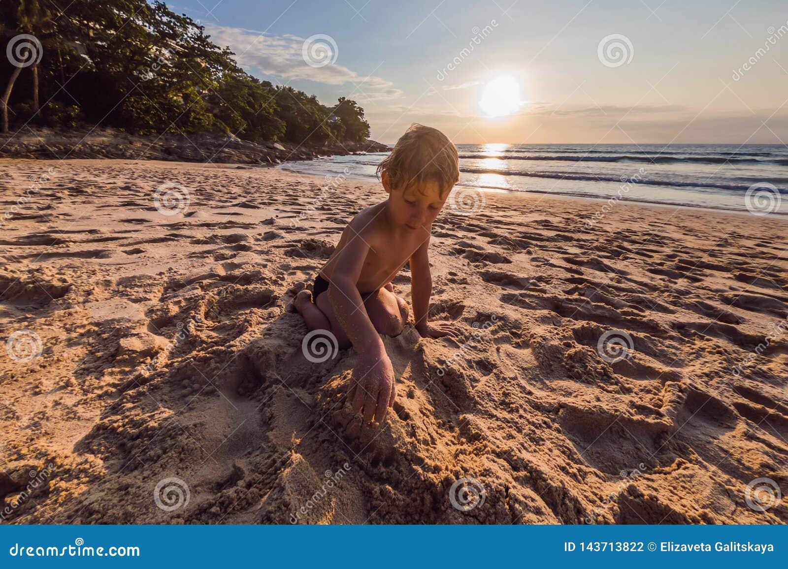 Muchacho lindo feliz que juega en la playa