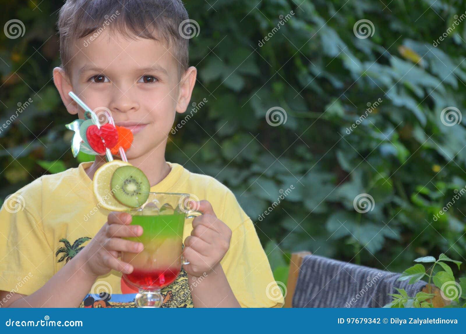 Muchacho lindo que bebe el smoothie sano del zumo de frutas del cóctel en verano Niño feliz que disfruta de la bebida orgánica