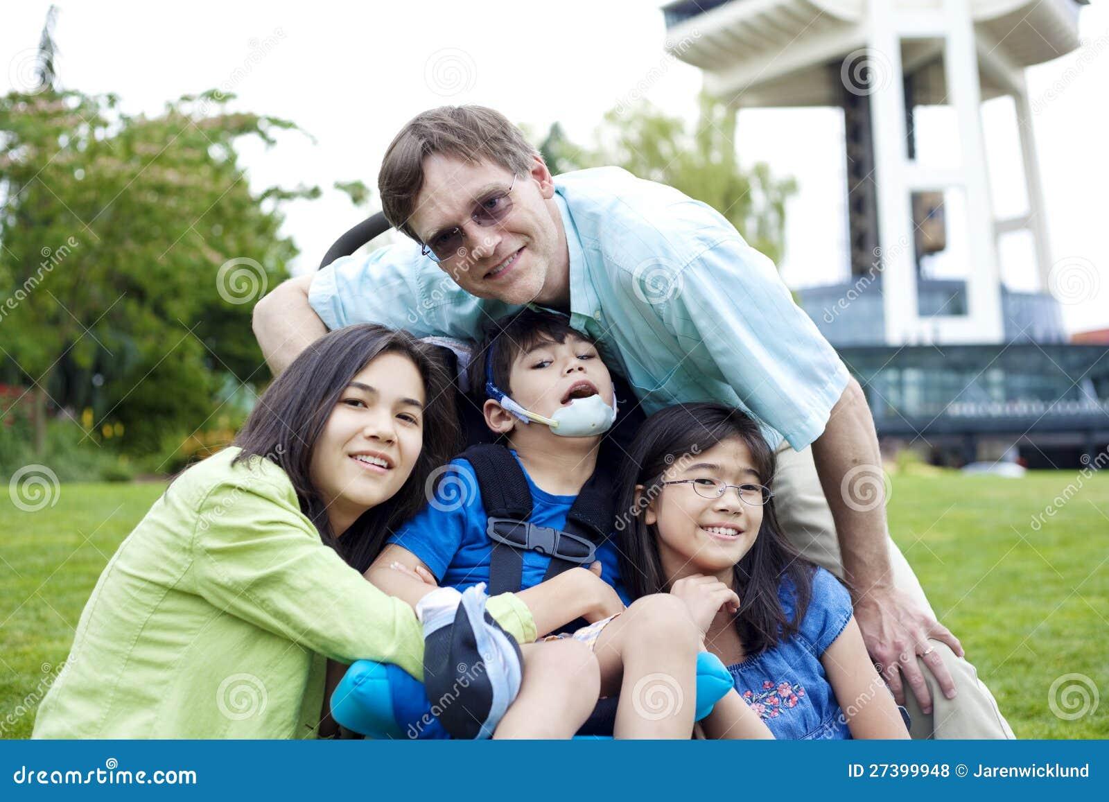 Muchacho lisiado en el sillón de ruedas rodeado por la familia