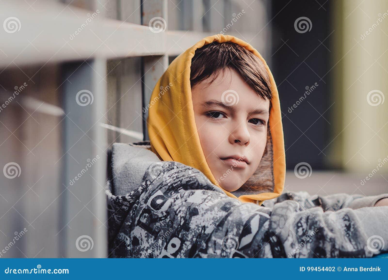 Muchacho Pre-adolescente en una calle en una ciudad grande al lado de un edificio alto solamente