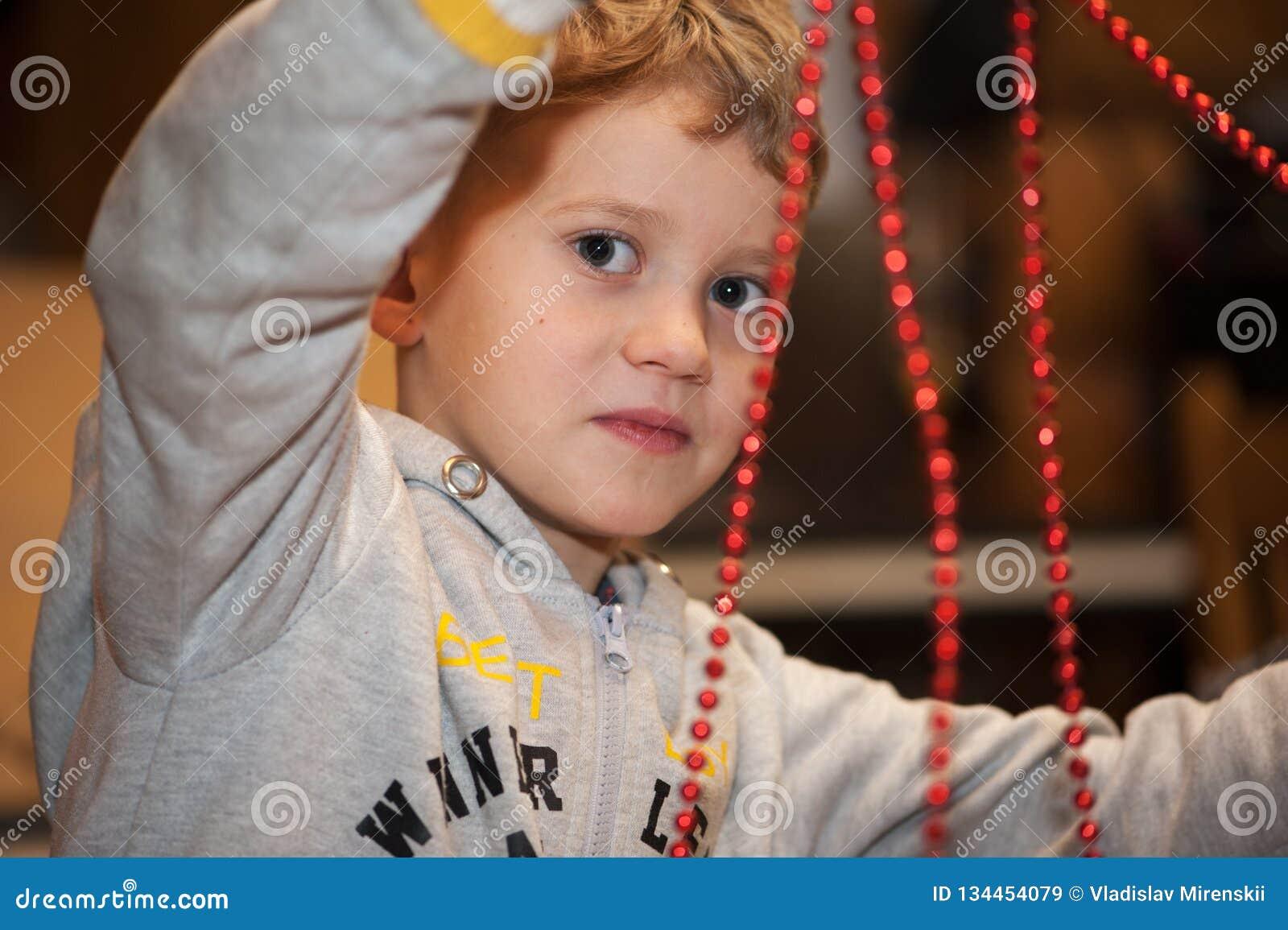 Muchacho que hace la decoración de la Navidad de gotas rojas