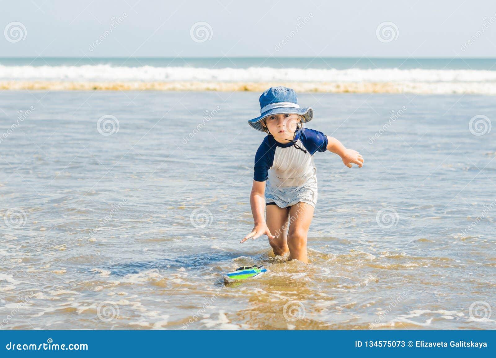 Muchacho que juega en la playa en el agua