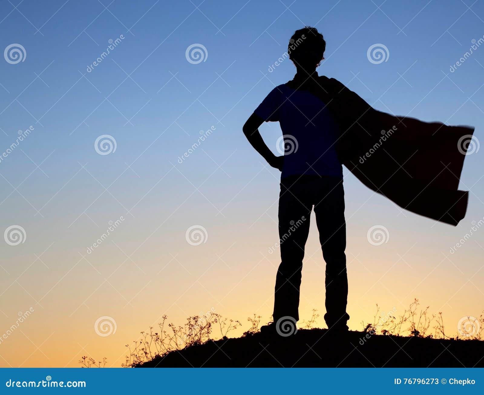 Muchacho que juega a super héroes en el fondo del cielo, silueta de la camiseta