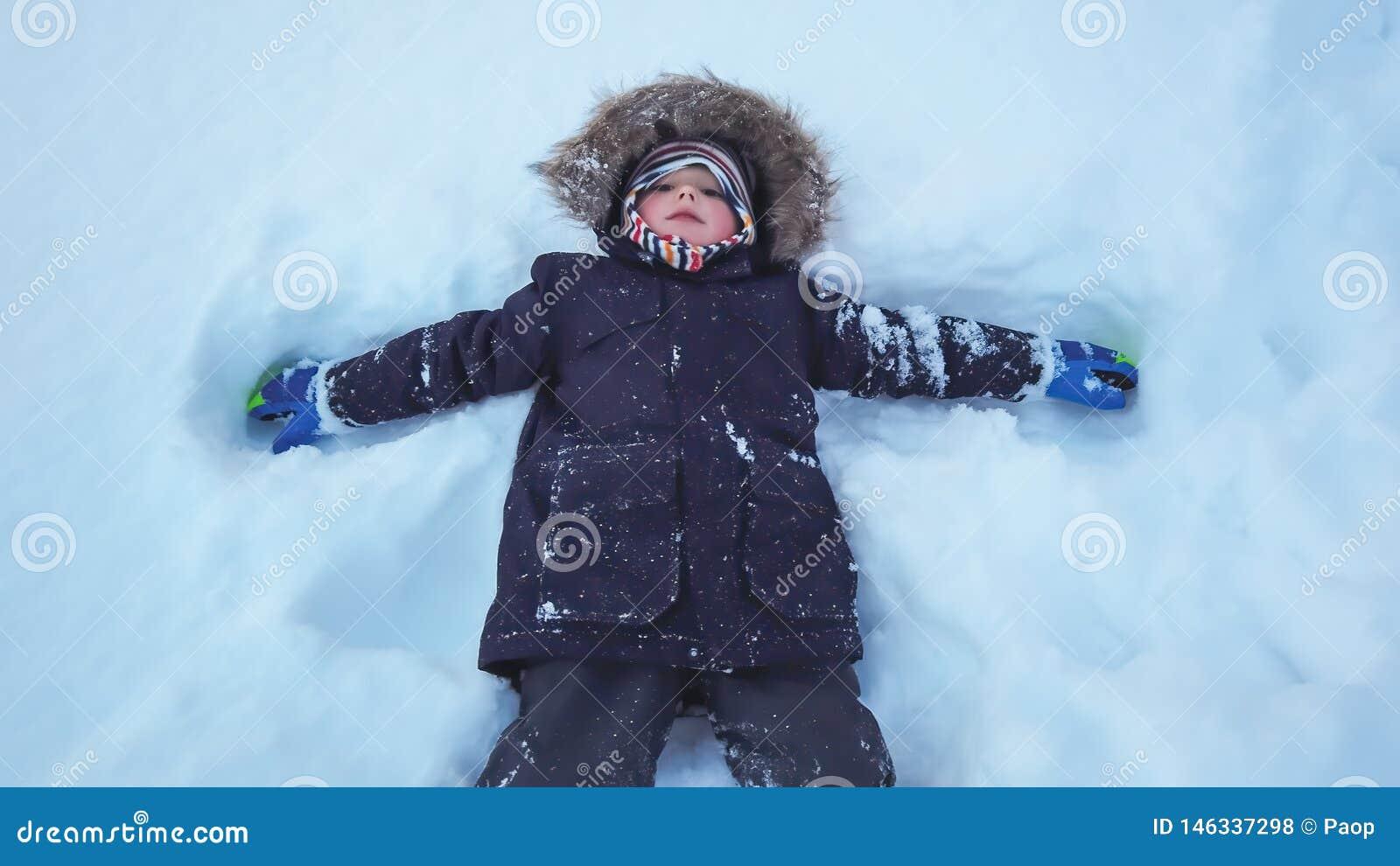 Muchacho que miente en una nieve profunda