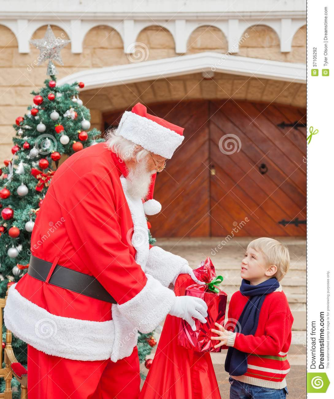 Muchacho que mira a Santa Claus While Taking Gift From