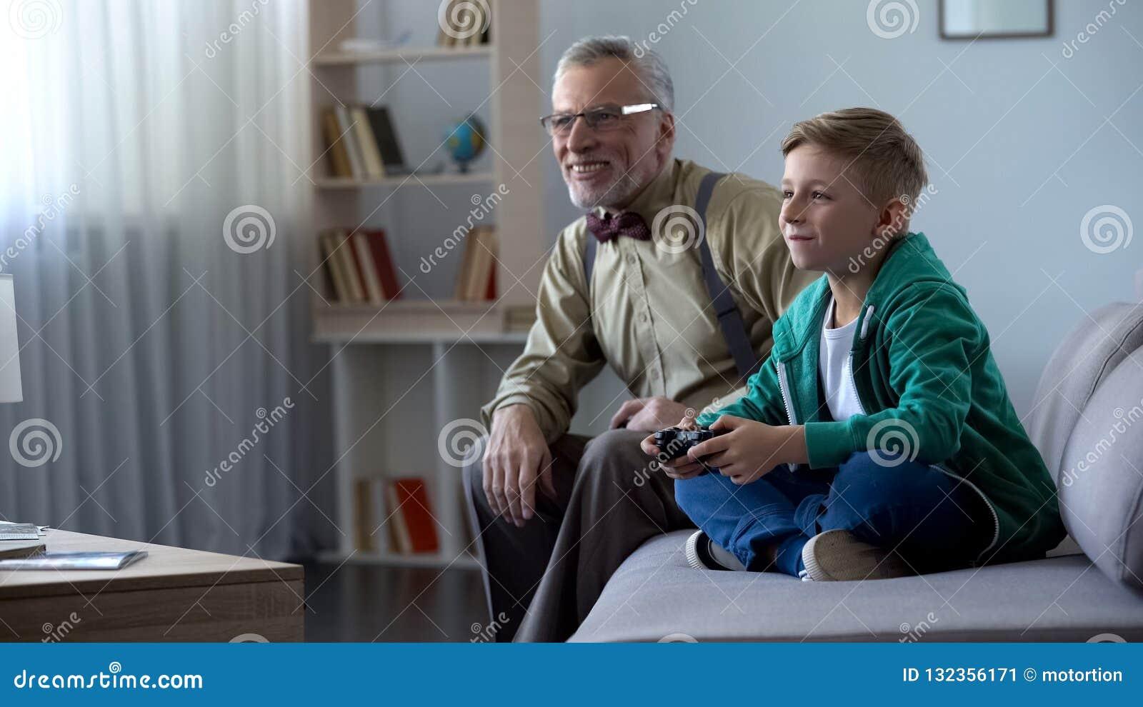 Muchacho que muestra el videojuego de abuelo, jugando con la consola, tiempo feliz junto