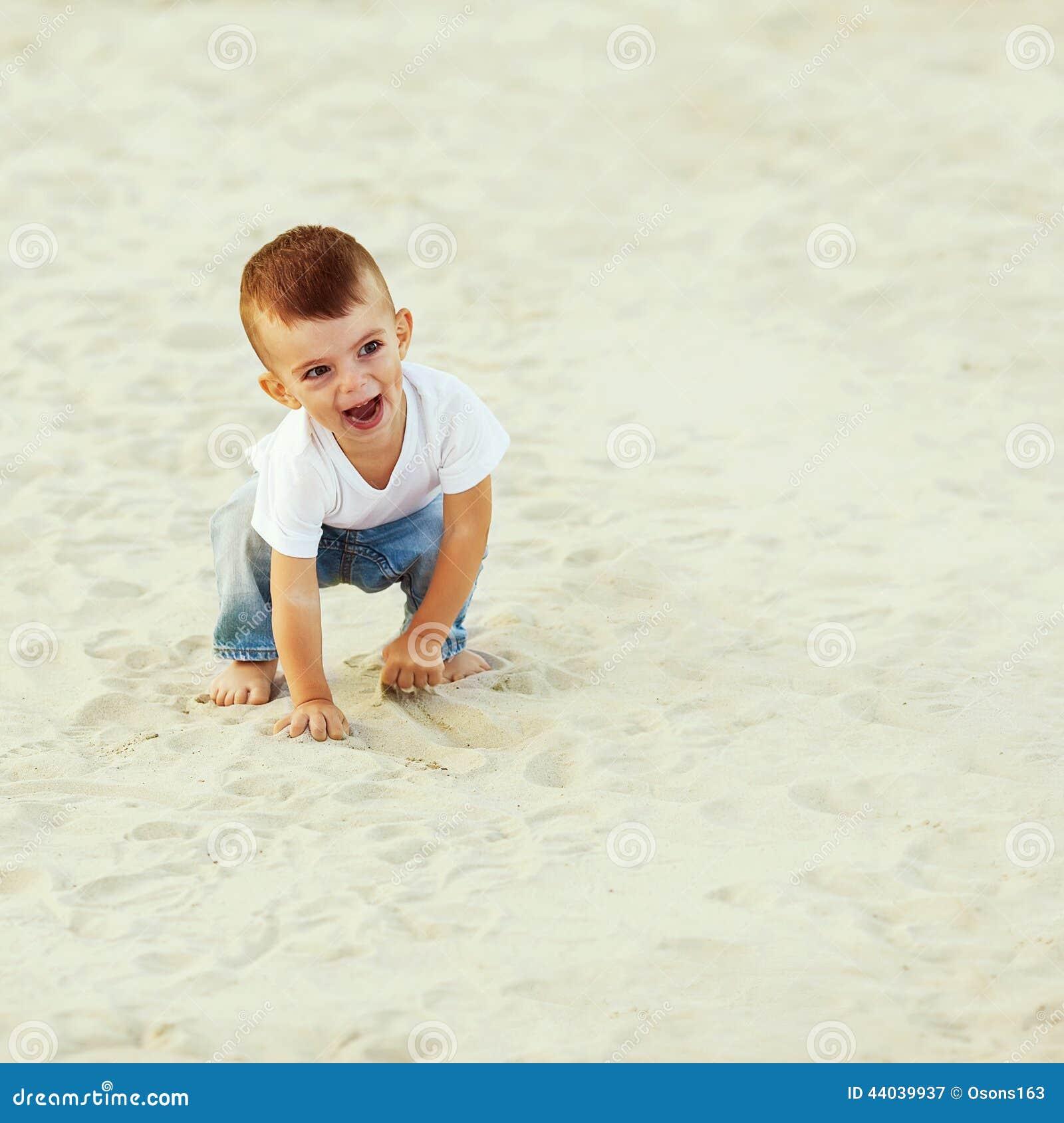 Muchacho que ríe en la arena