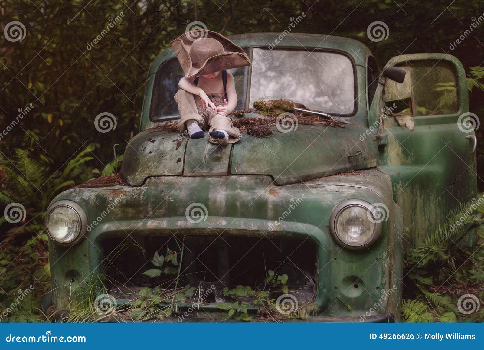 Muchacho que se sienta en el camión quebrado