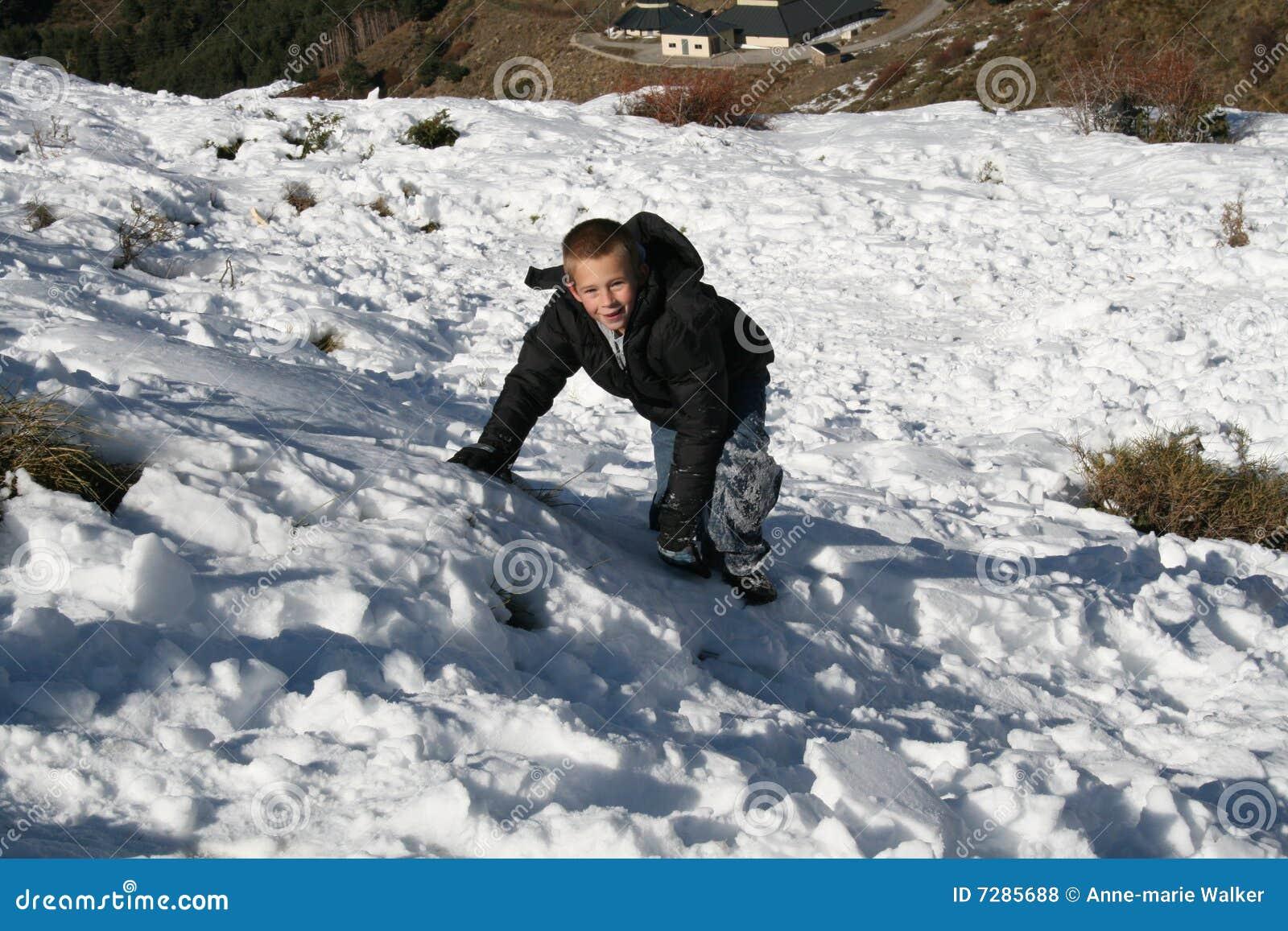 Muchacho que sube en la nieve