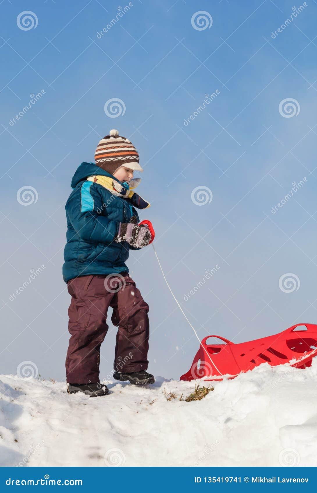Muchacho que tira del trineo plástico rojo a una colina nevosa