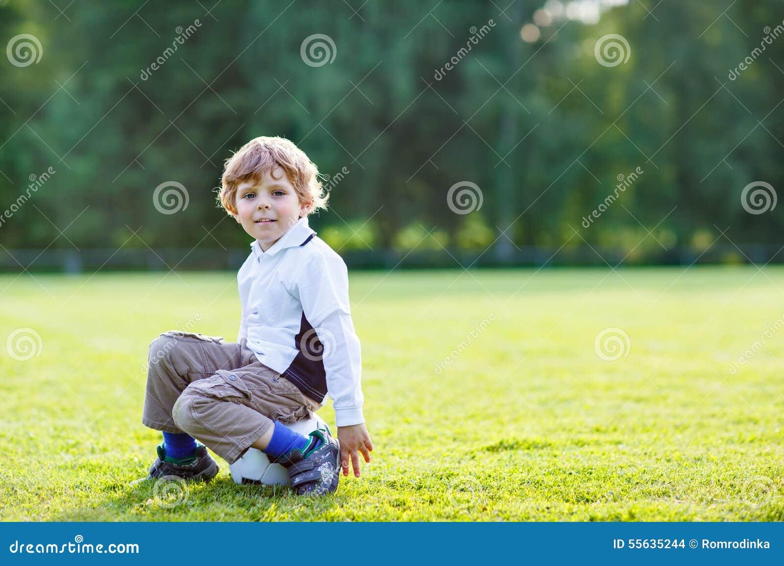 Muchacho rubio de 4 que descansan con fútbol en campo de fútbol