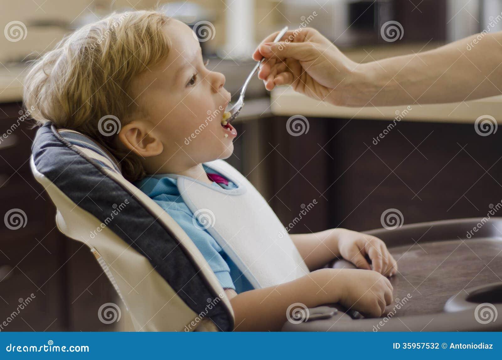 Muchacho rubio que es alimentado por su mamá