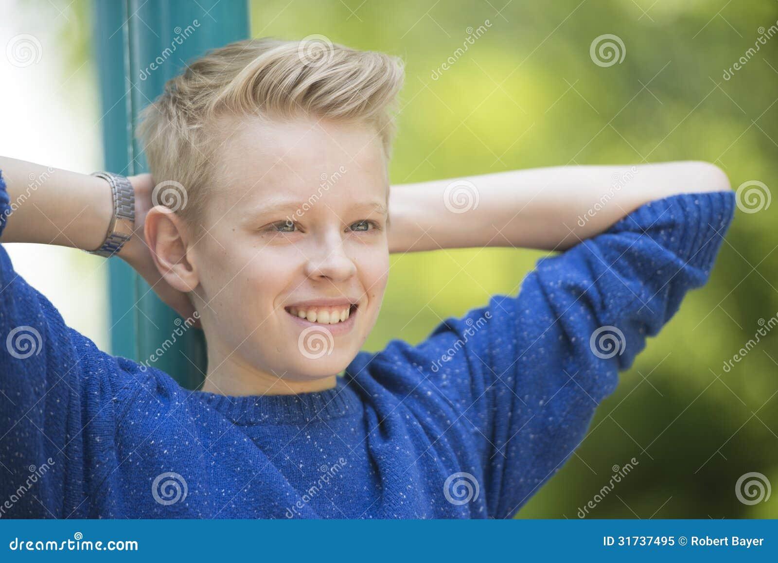 Muchacho sonriente relajado feliz del adolescente al aire libre