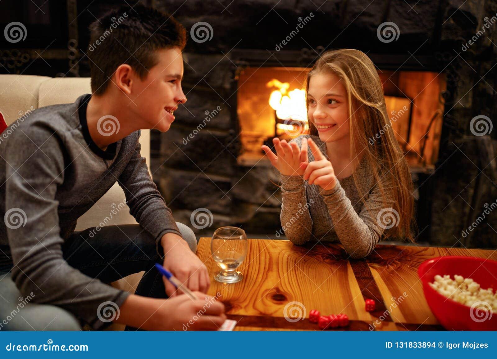 Muchacho sonriente y su hermana que se divierten que juega al juego