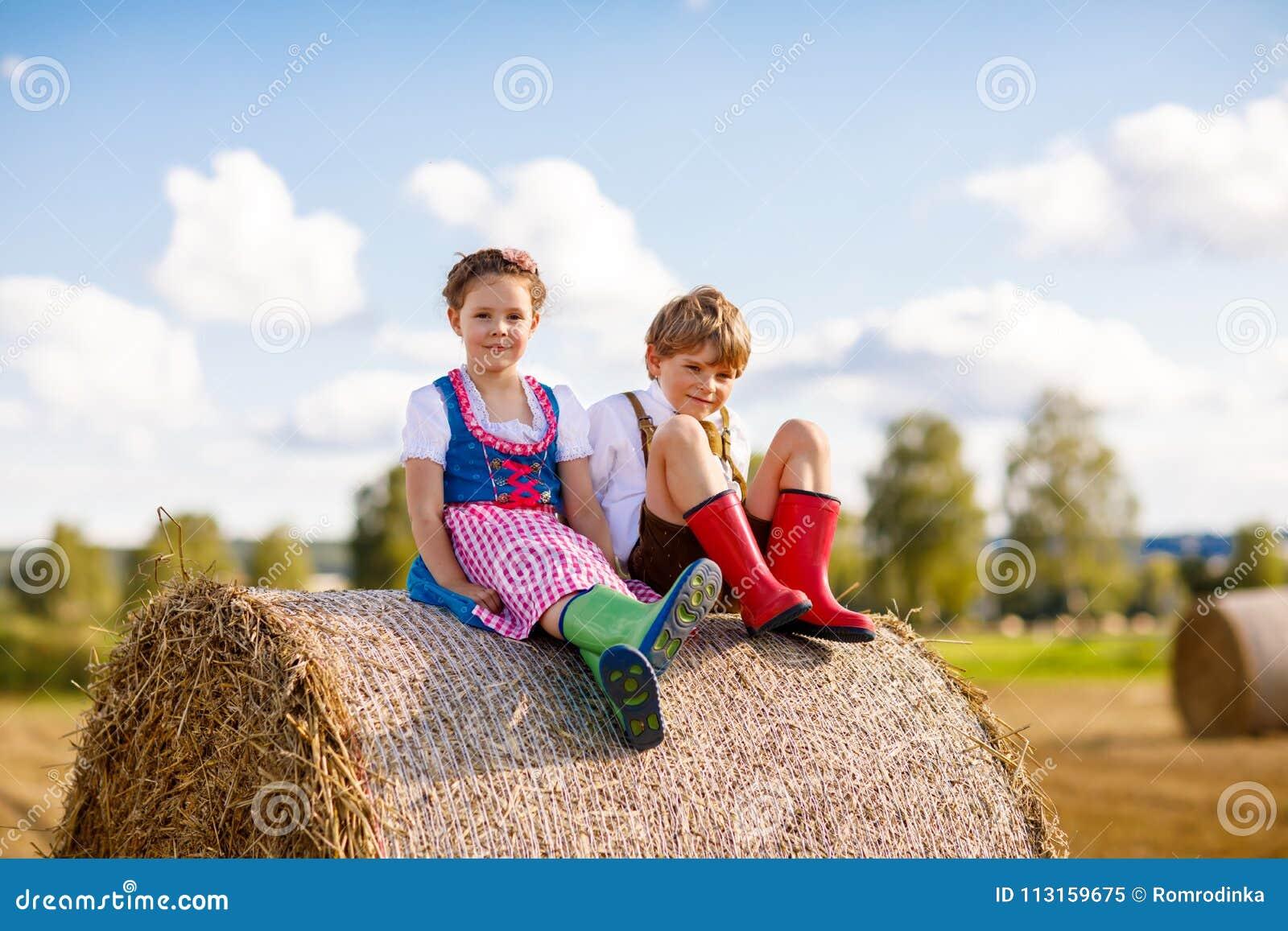 Muchacho y muchacha adorables del niño en trajes bávaros tradicionales en campo de trigo en pila del heno