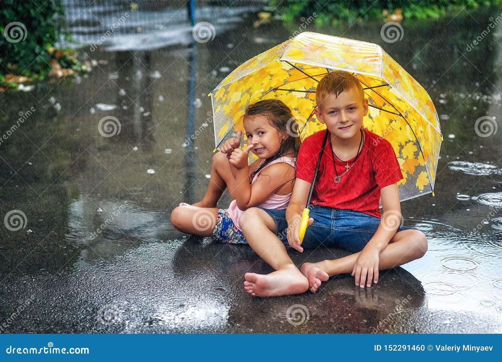 Muchacho y muchacha alegres con el paraguas durante la lluvia del verano