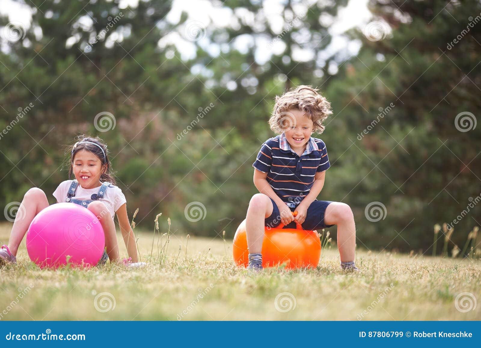 Muchacho y muchacha que se sientan en spacehooper