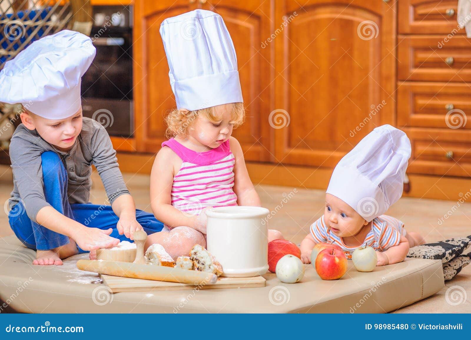 f29fa5a57bc6f Dos hermanos - muchacho y muchacha - y un niño recién nacido con ellos en los  sombreros del ` s del cocinero que se sientan en el piso de la cocina  manchado ...