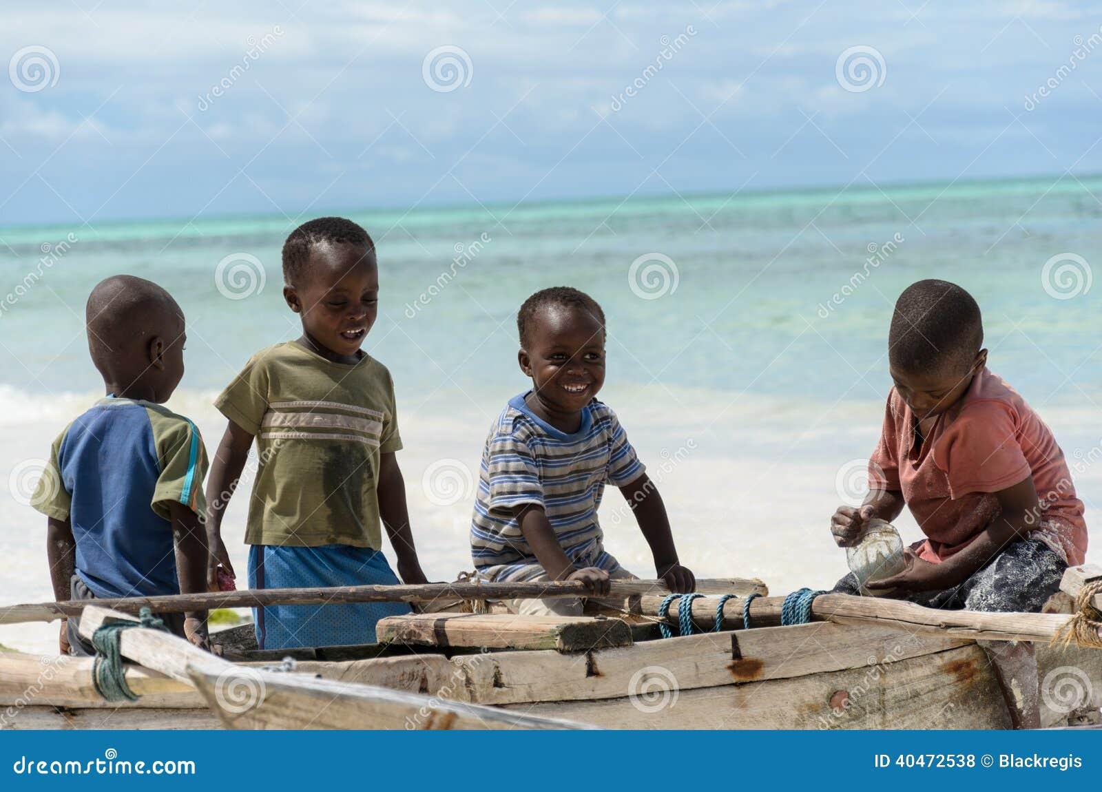 Muchachos africanos felices jovenes en el barco de pesca