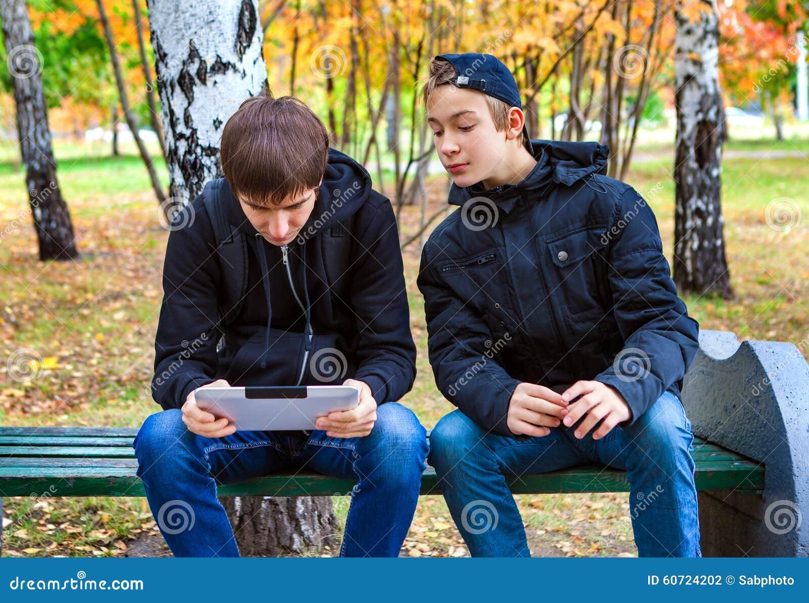 Muchachos con la tableta al aire libre