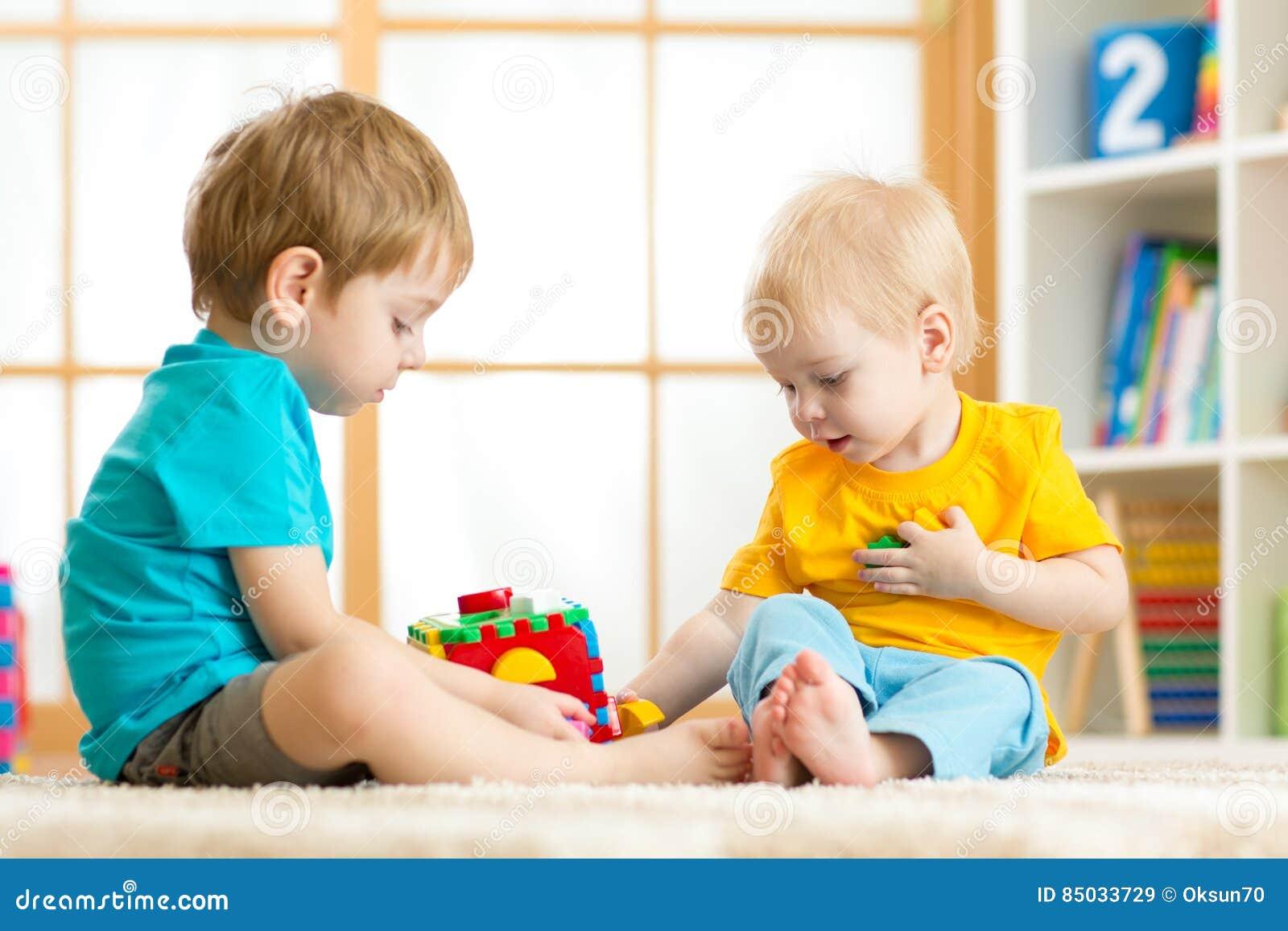 Muchachos del preescolar del niño de los niños que juegan el juguete lógico que aprende formas y colores en casa o cuarto de niño