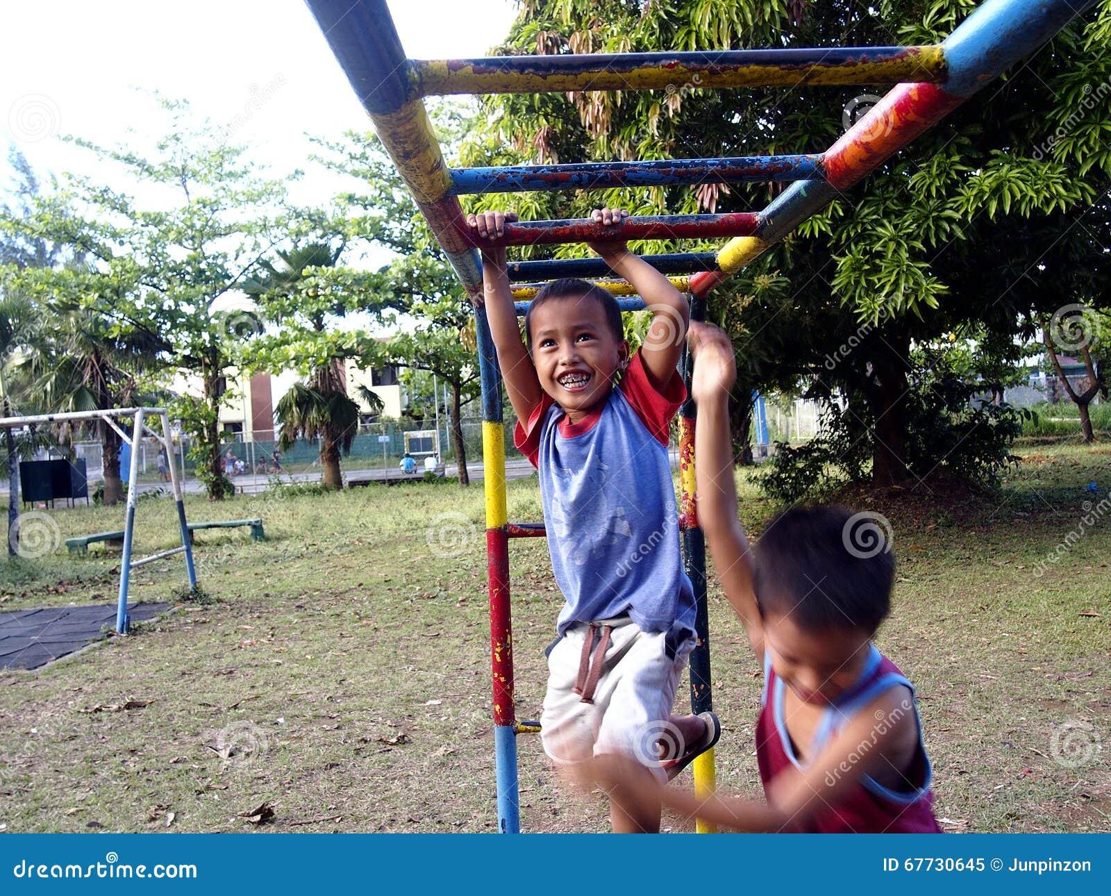 Muchachos jovenes y muchachas que juegan en un patio en la ciudad de Antipolo, Filipinas