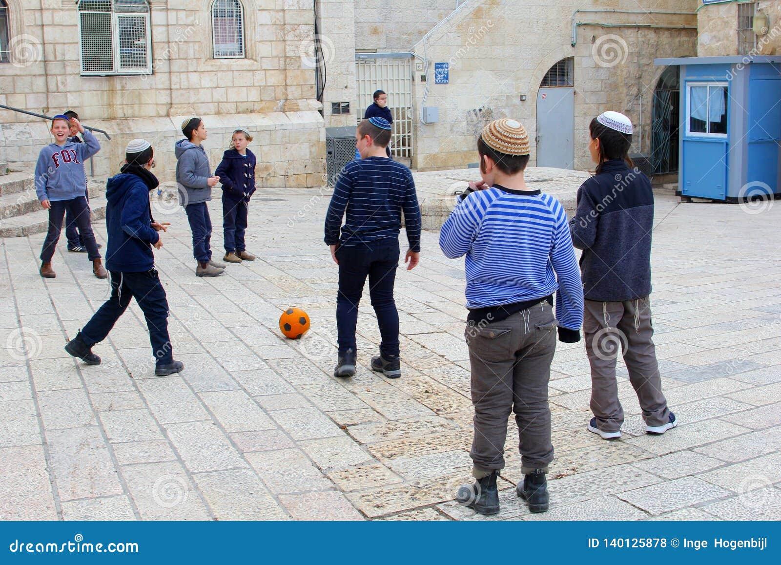 Muchachos judíos que juegan el treet al aire libre del fútbol, cuarto judío, Jerusalén