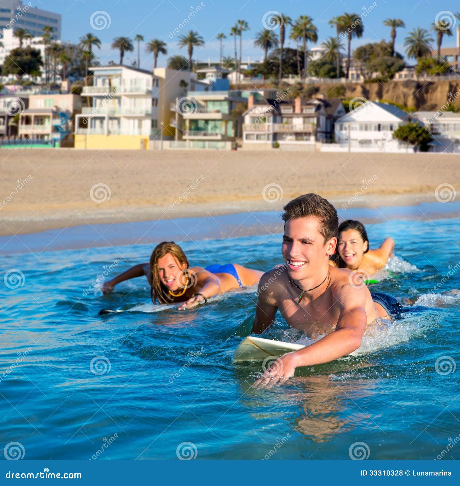 Muchachos y muchachas de la persona que practica surf del adolescente que nadan la tabla hawaiana del ove