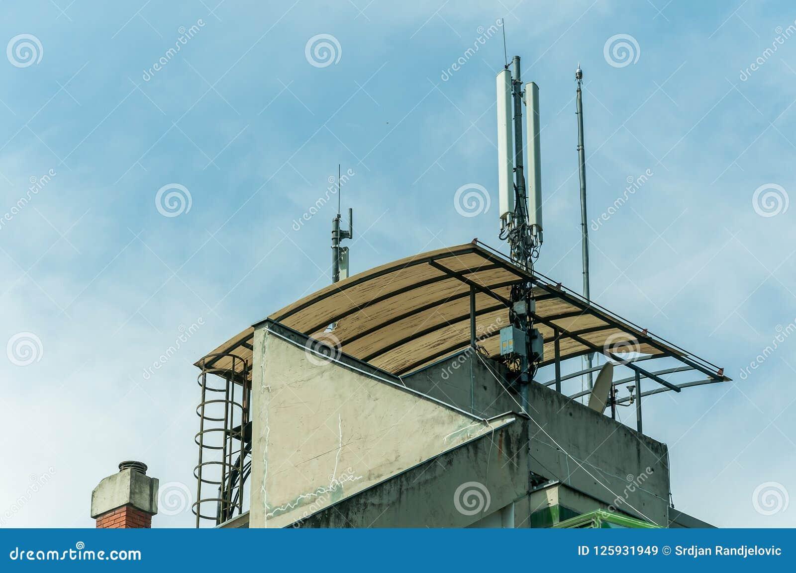Muchas antenas de receptores del teléfono celular de la telecomunicación en el top del tejado del edificio residencial con el fon