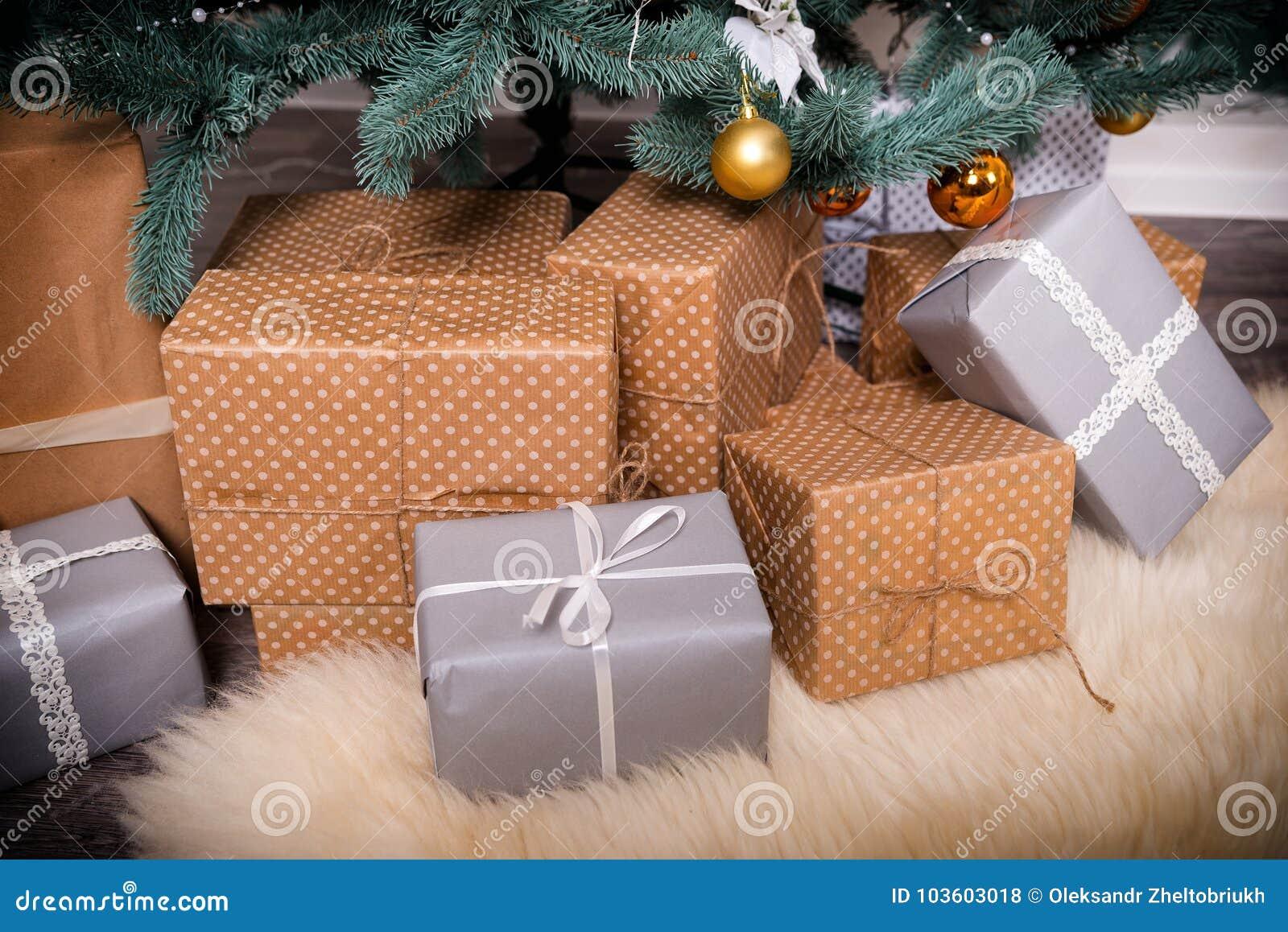 Muchas cajas con los regalos de la Navidad debajo del árbol de navidad