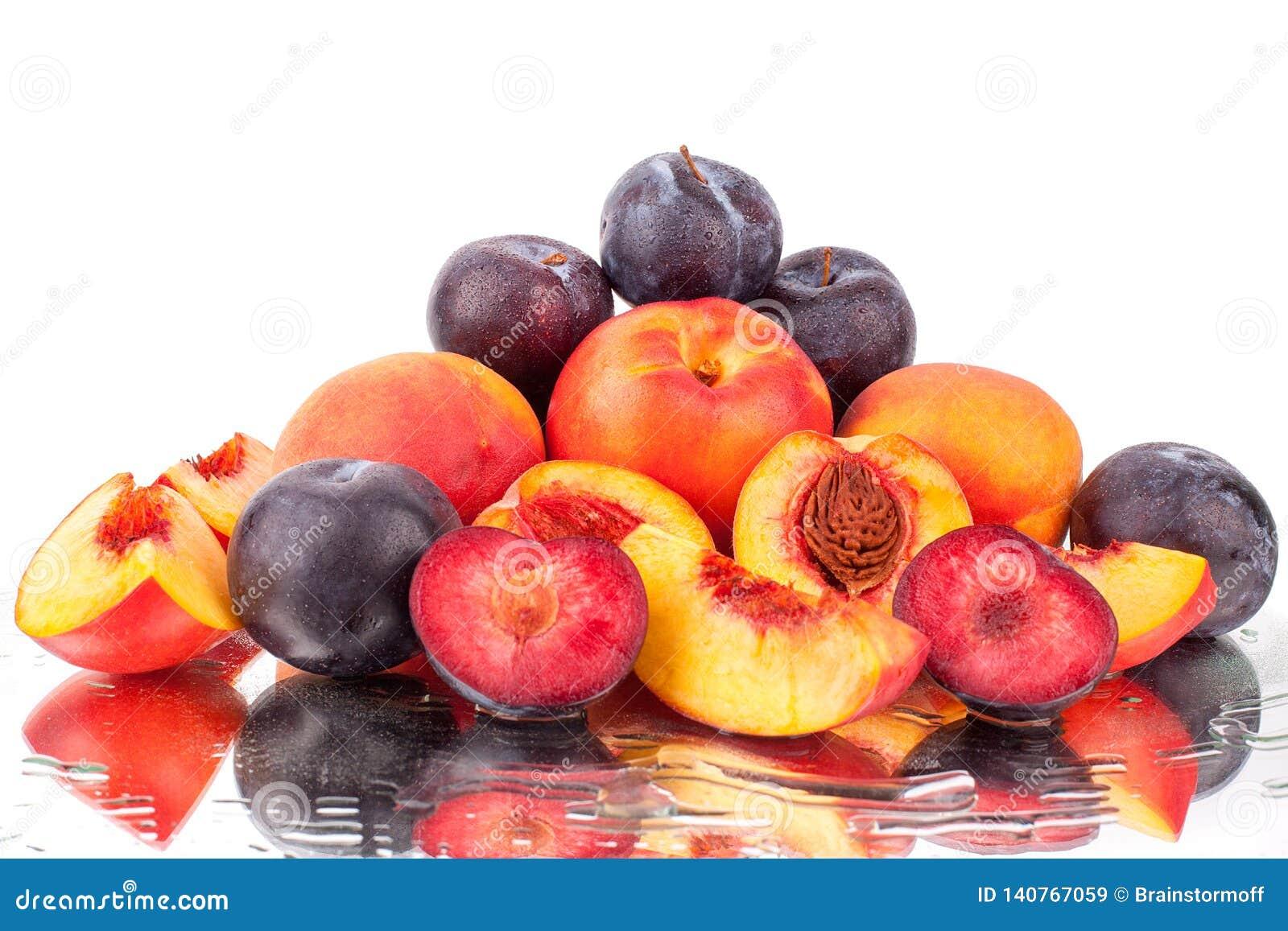 Muchas frutas brillantes, melocotones y ciruelos enteros y del corte en un fondo blanco del espejo en agua caen aislado