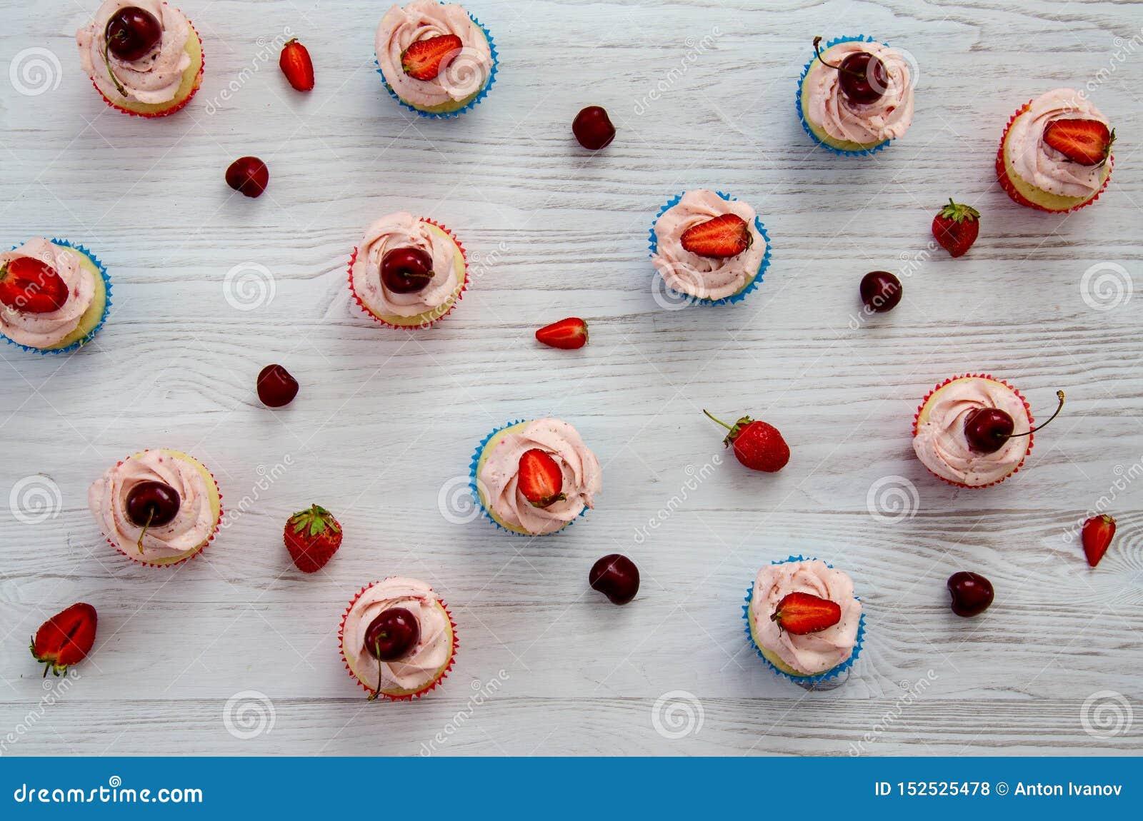 Muchas magdalenas con la crema y las fresas blancas en una tabla de madera