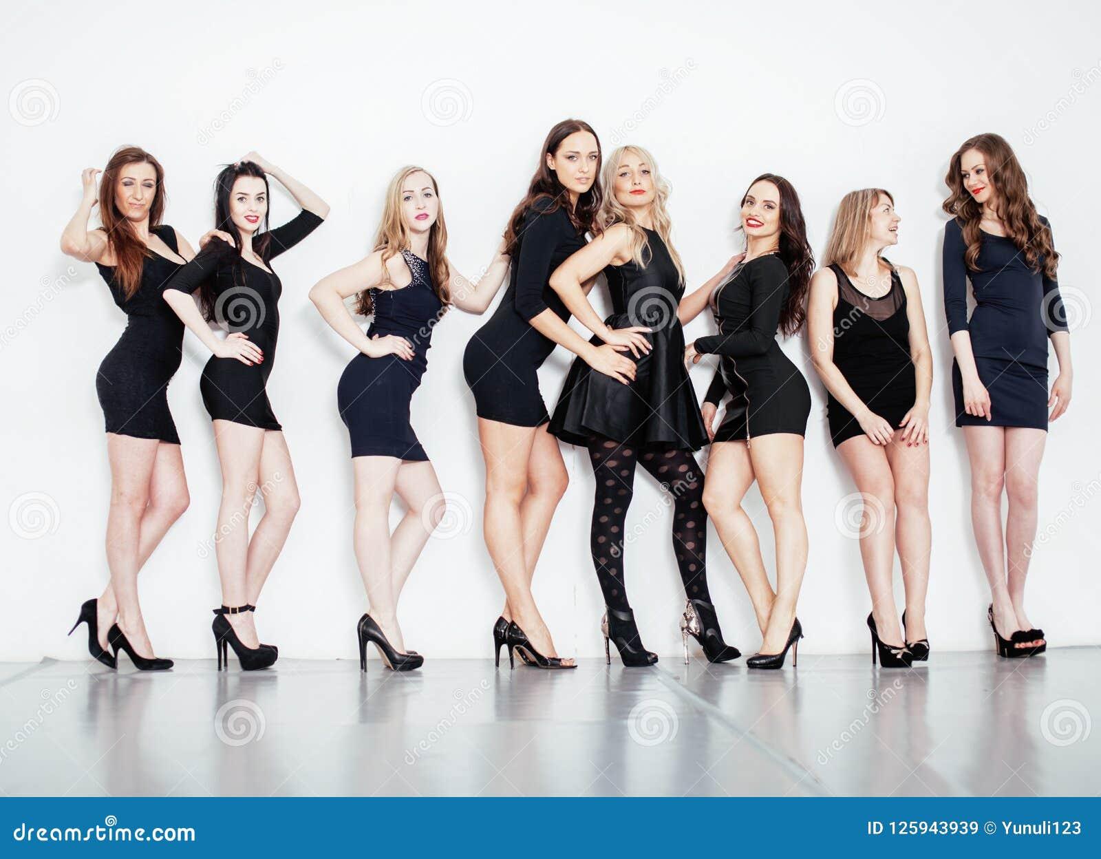 Muchas mujeres diversas en línea, pequeños vestidos negros de lujo que llevan,