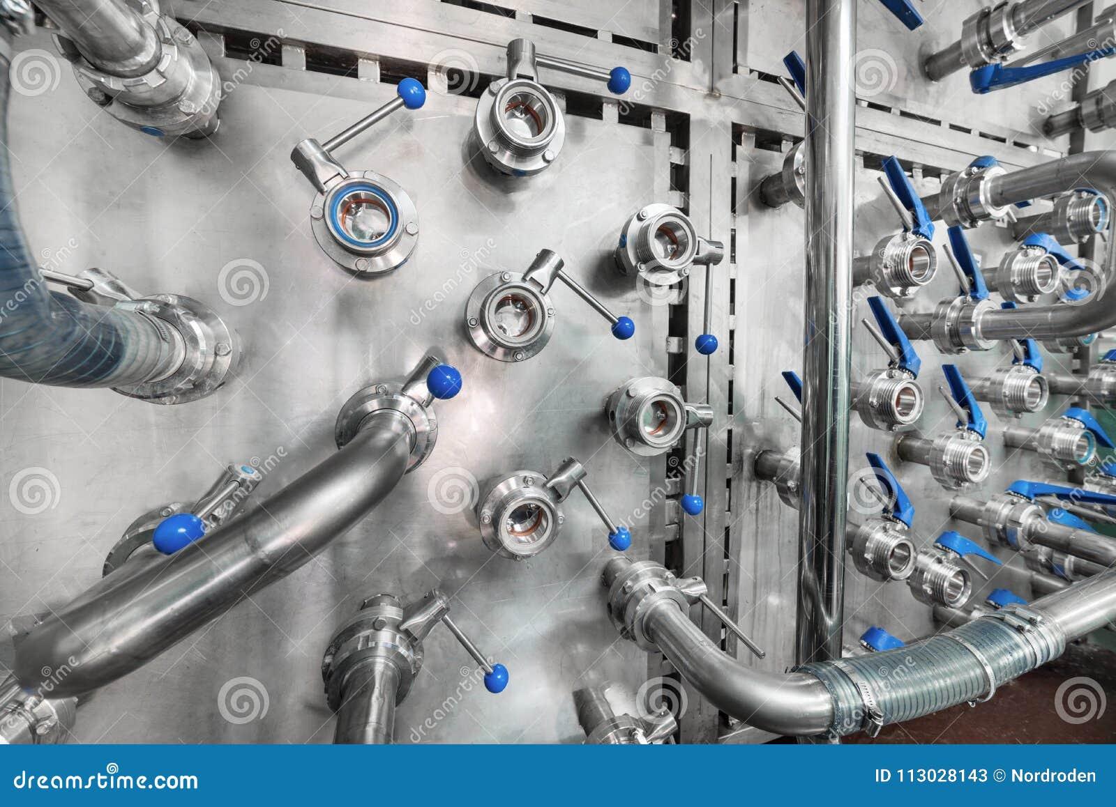 Muchas vávulas de bola de acero con las manijas del azul montaron en una pared del metal