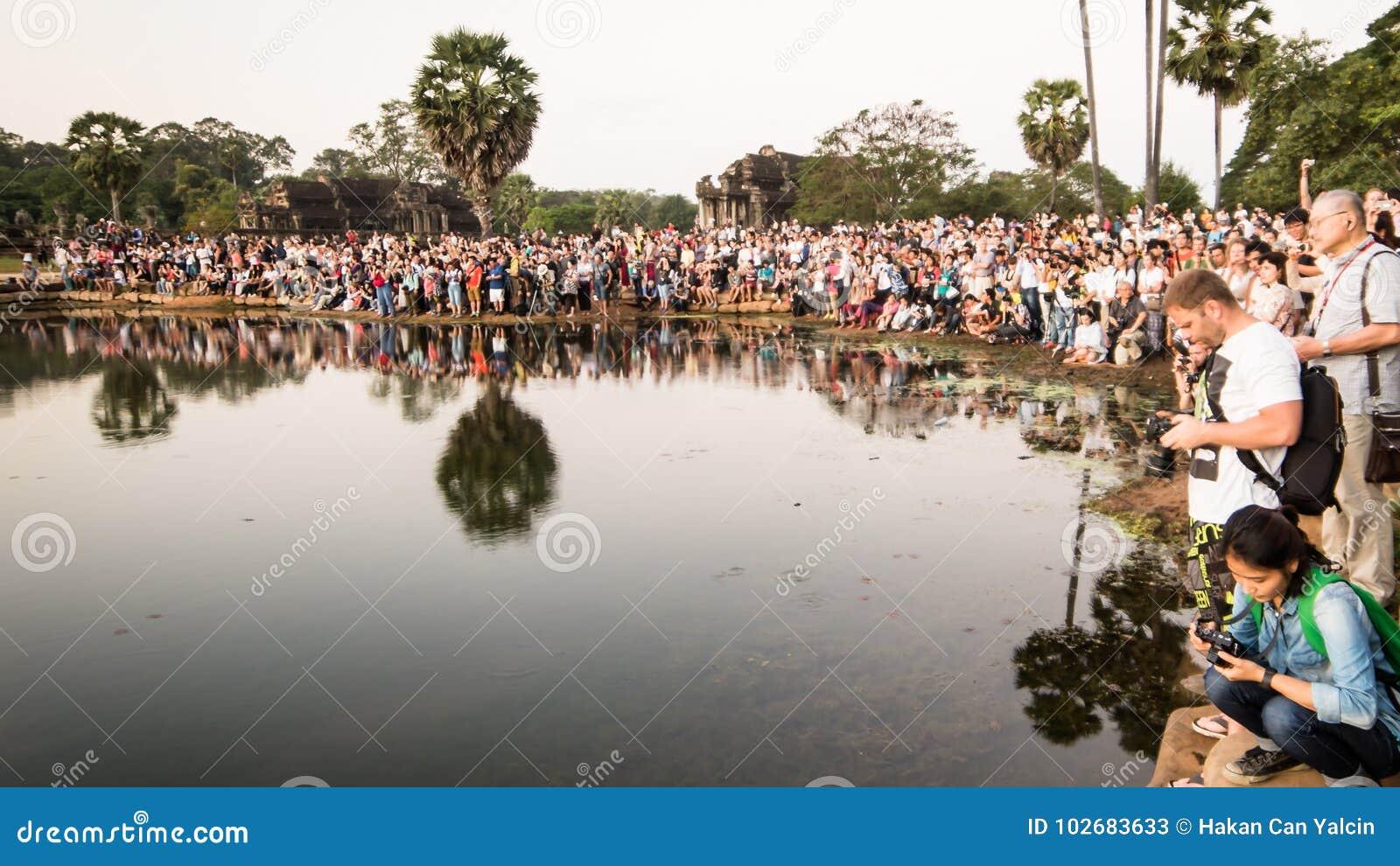 Muchedumbre de turistas que toman una foto de la salida del sol en Angkor Wat