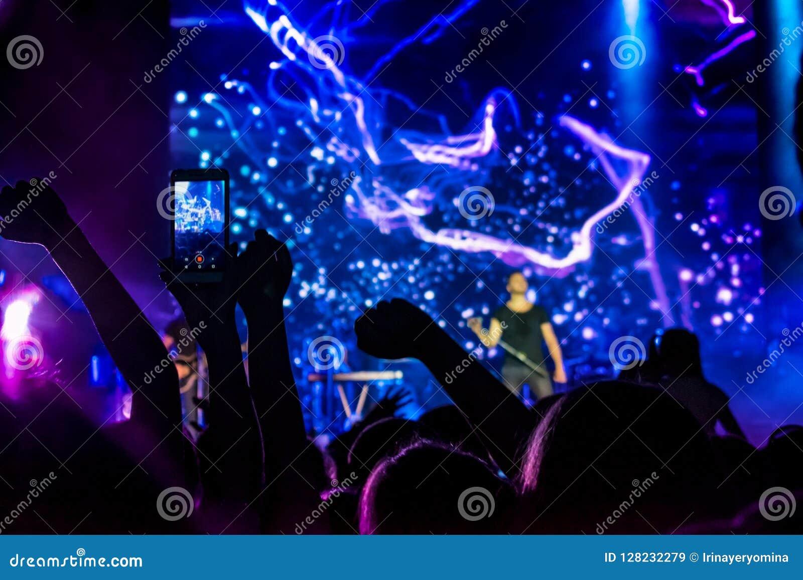 Muchedumbre en el concierto Siluetas de la gente en retroiluminado por las luces azules y púrpuras brillantes de la etapa Muchedu
