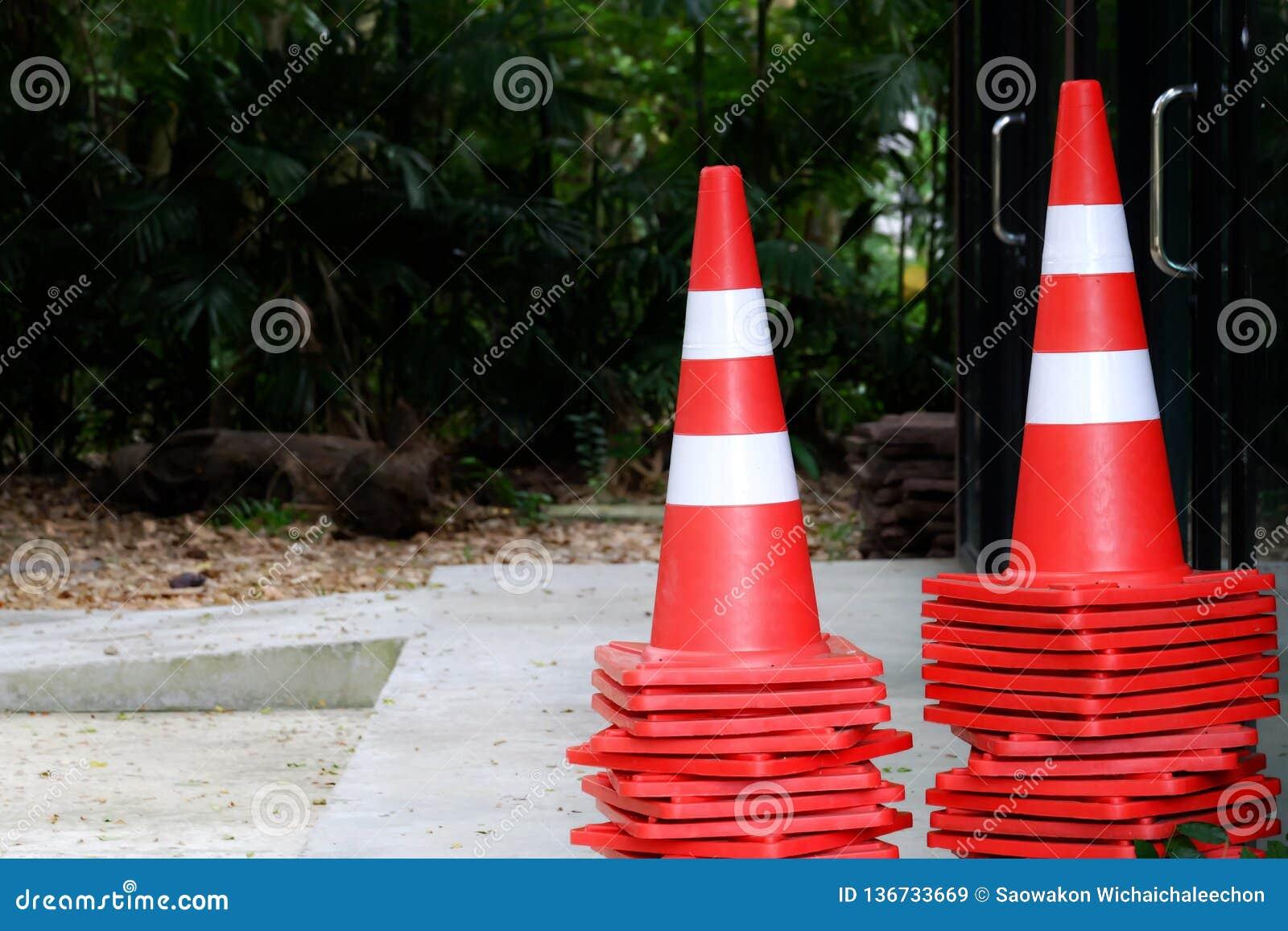Muchos conos del tráfico en piso del cemento delante del edificio