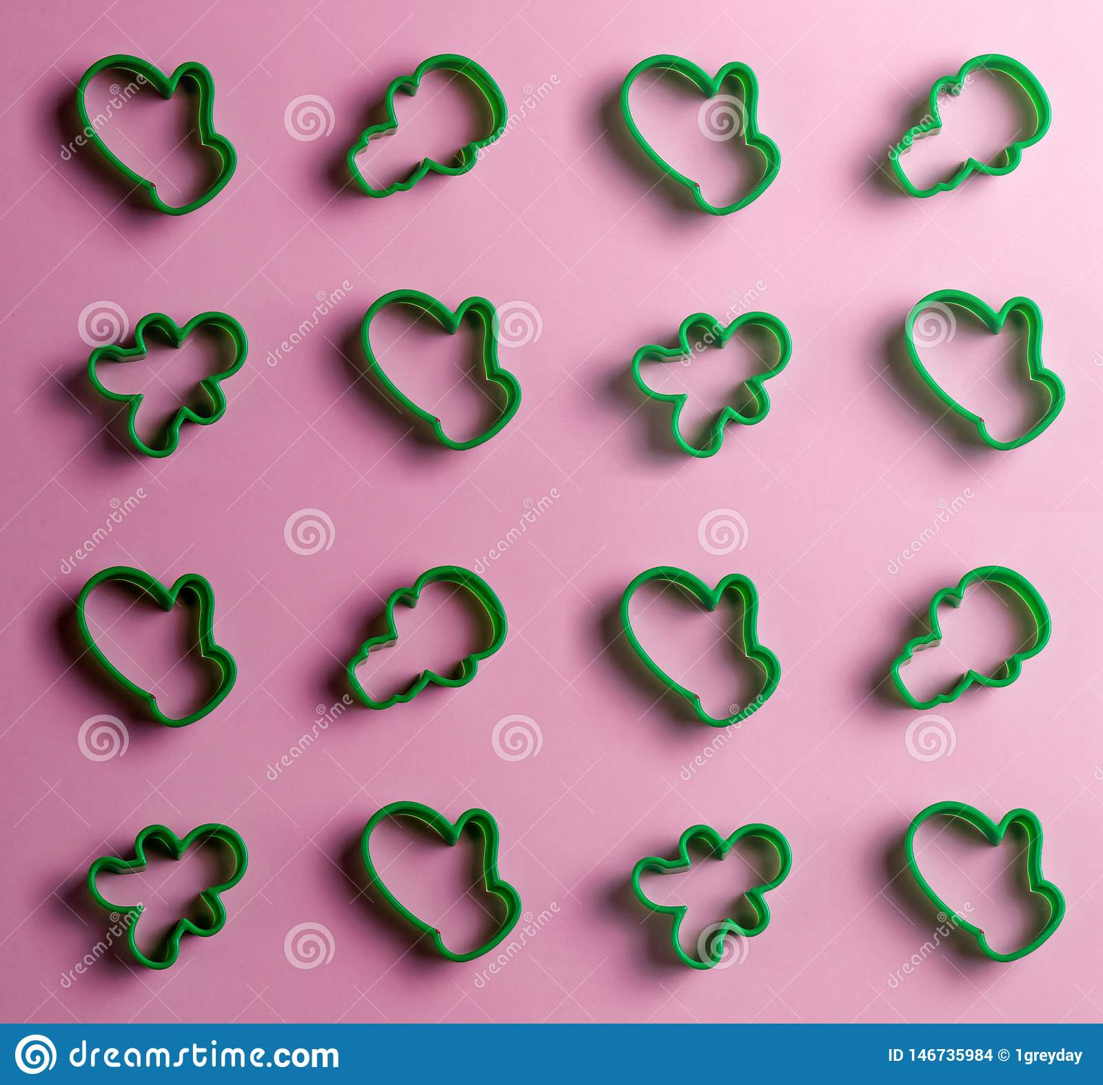 Muchos cortadores de la galleta aislados en el fondo rosado