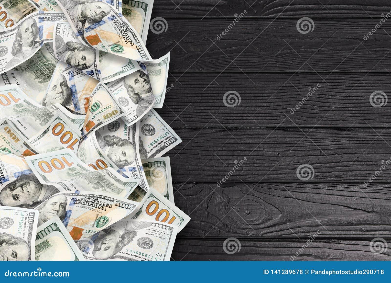 Muchos dólares en un fondo de madera negro
