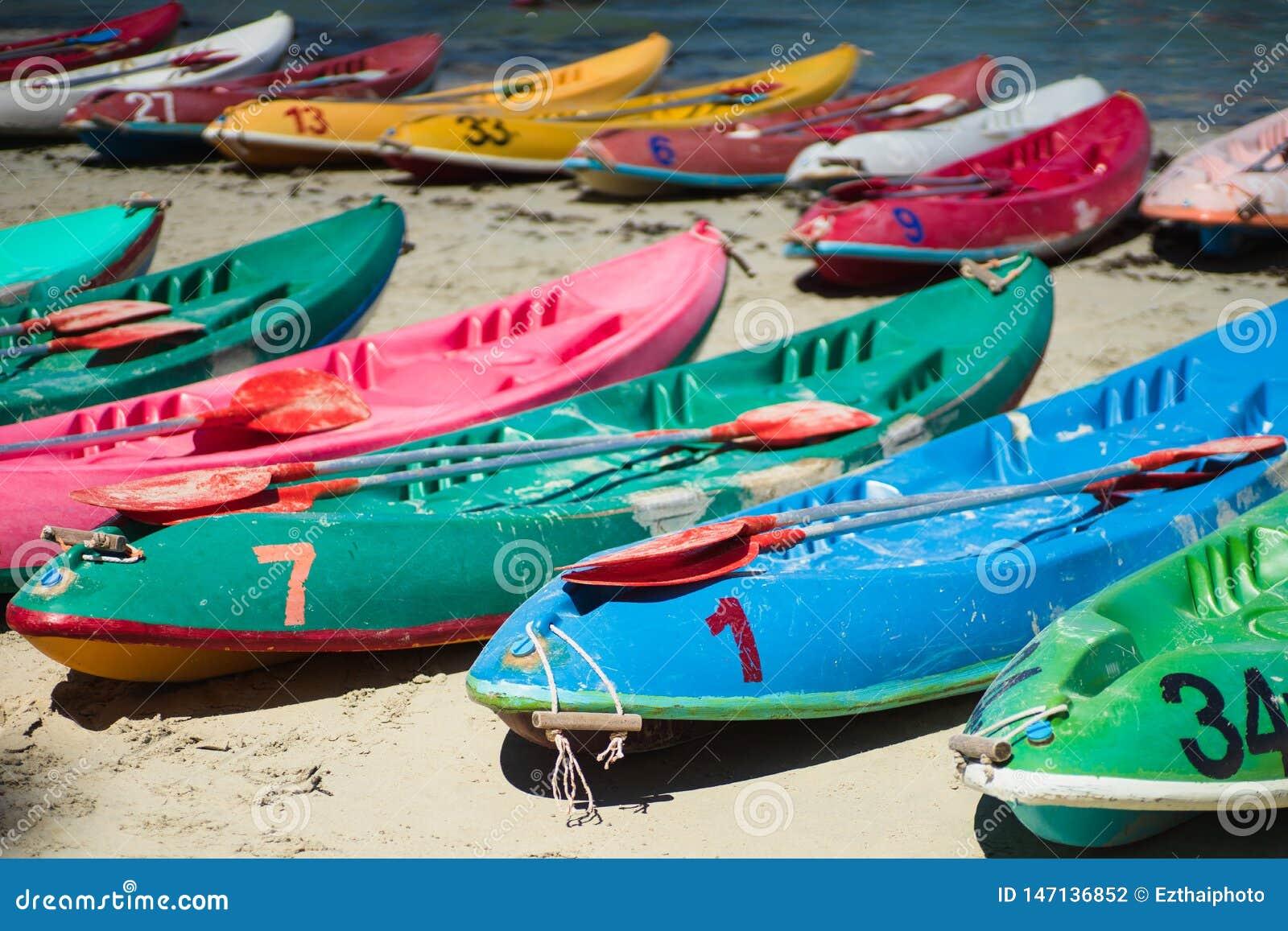 Muchos kajaks viejos coloridos de las canoas en la playa en la playa del ron de Nang, Sattahip, Chonburi, Tailandia