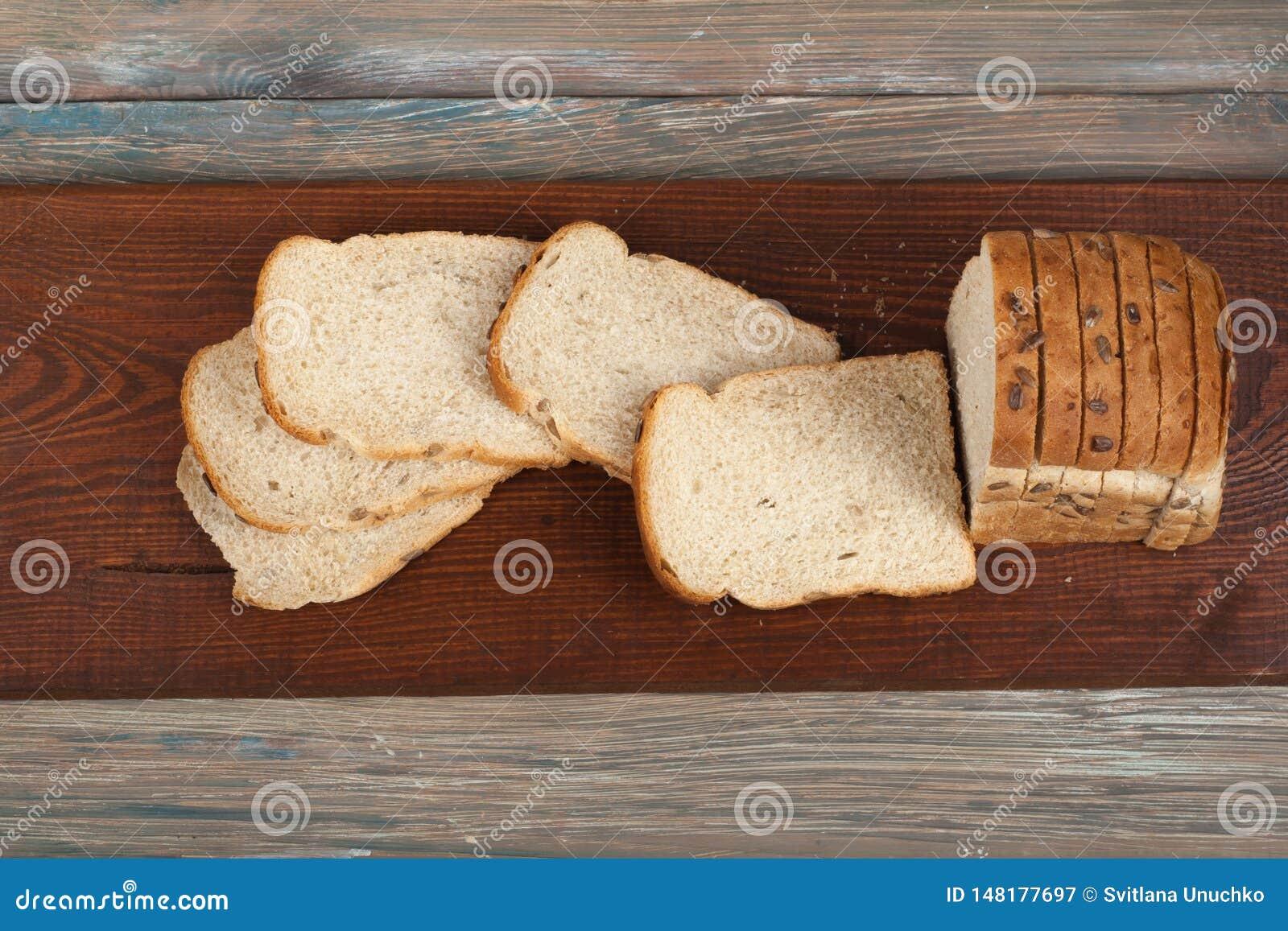 Muchos panes y rollos mezclados del pan cocido en fondo de madera de la tabla Visi?n superior
