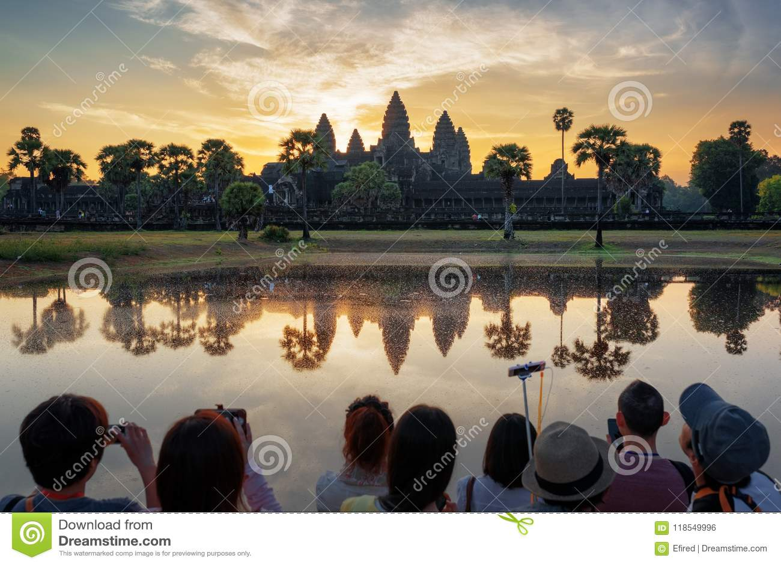 Muchos turistas asiáticos que toman la imagen de Angkor Wat en la salida del sol