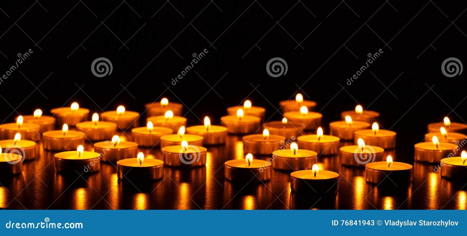 Muchos velas ardiendo con la profundidad del campo baja