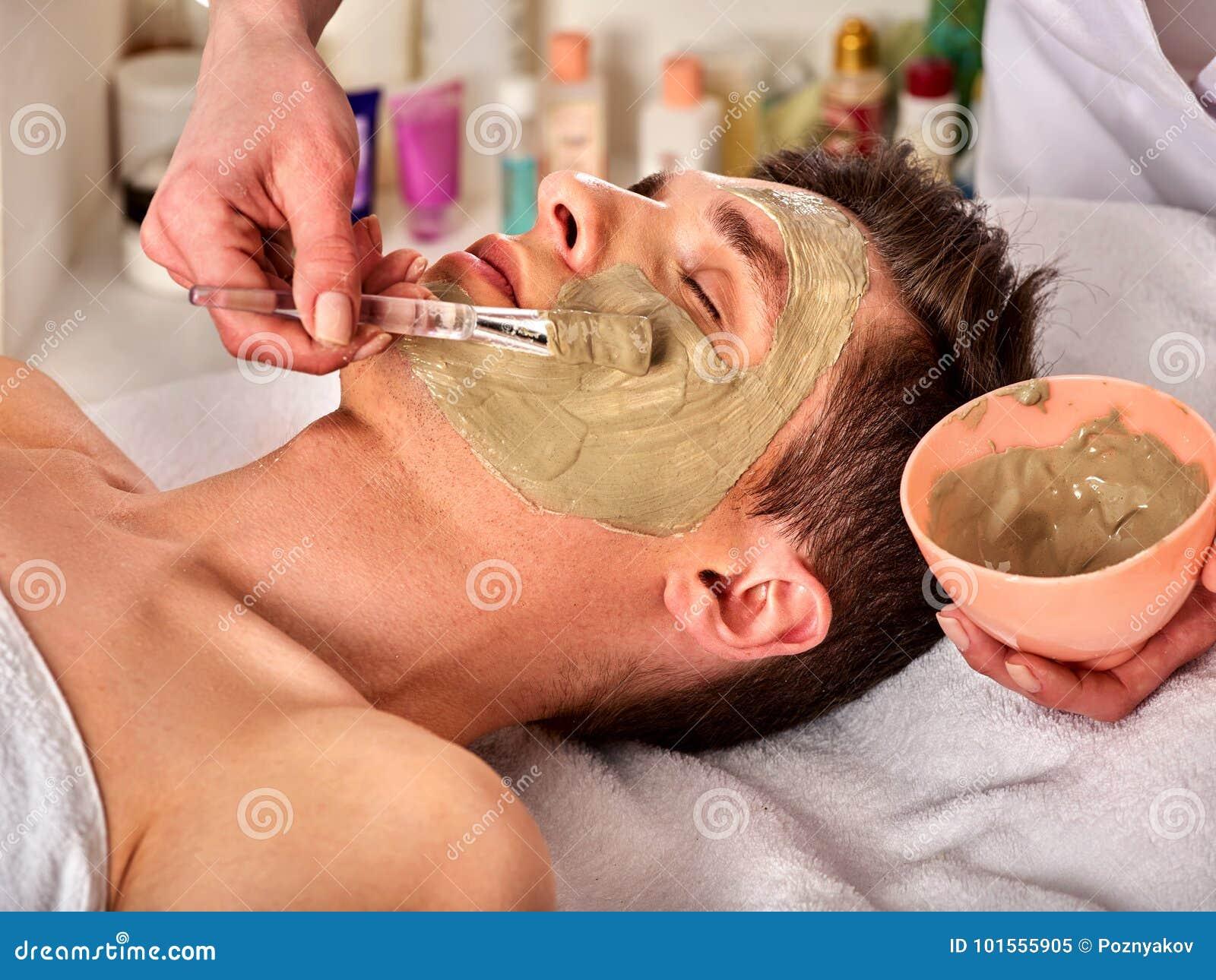 Mud facial mask of man in spa salon. Face massage .